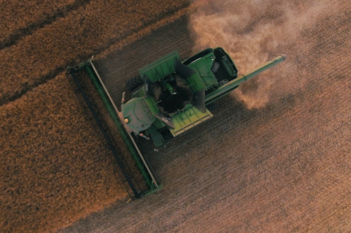 Picture taken from above of a combine machine, harvesting a dry field of grains.